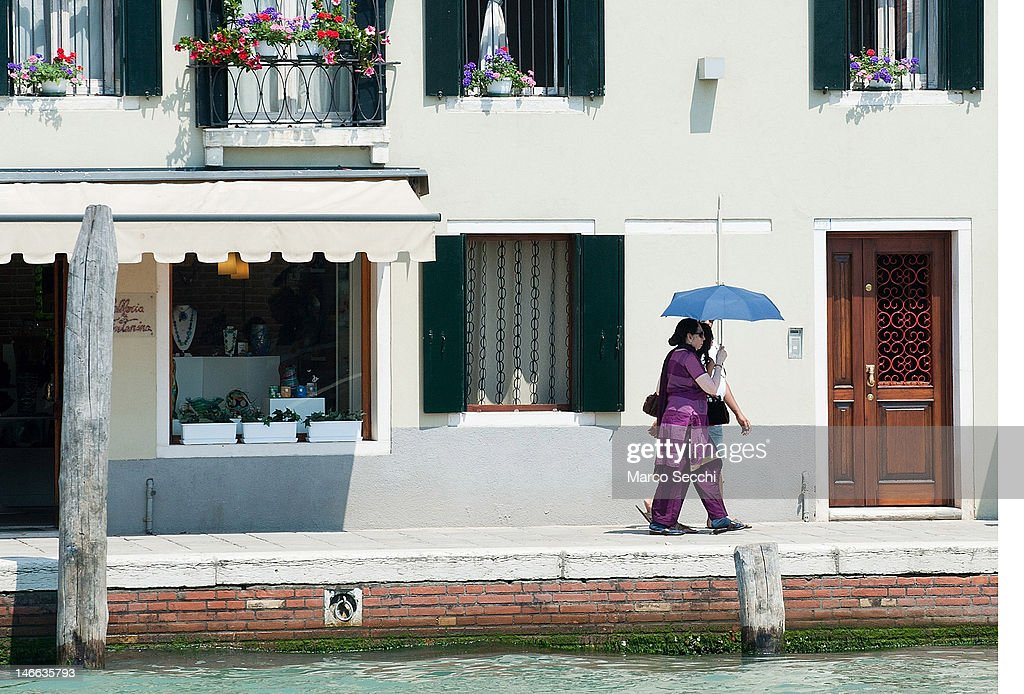 Two women walk under an umbrella on the Island of Murano on June 21, 2012 in Venice, Italy. An intense heatwave is sweeping across many regions in Italy, prompting the country's health ministry to issue a number of high level alerts.