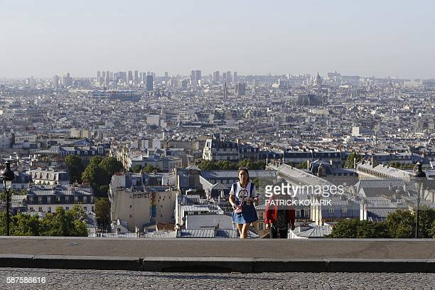 Two women walk up deserted steps near the SacreCoeur Basilica in the Montmartre neighborhood in Paris on August 9 2016 Many places and events in...
