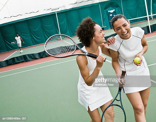 Two women walking and laughing in tennis court