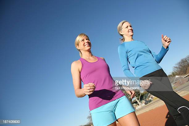 Two Women Walking Around A Track In Spring