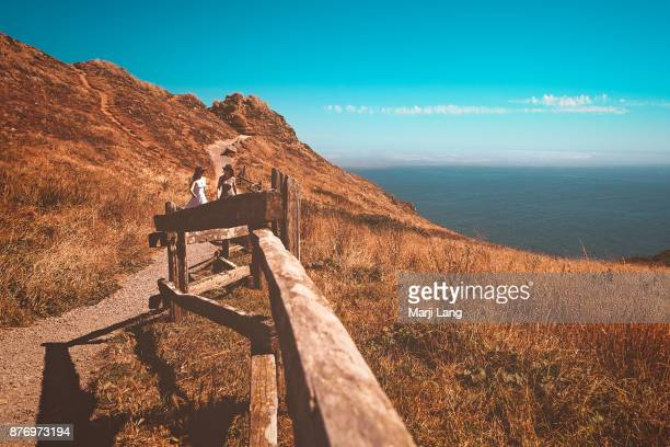 Two women walking on a coastline footpath by the Pacific ocean at Point Reyes National Seashore USA
