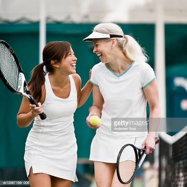 Two women walking on tennis court, laughing