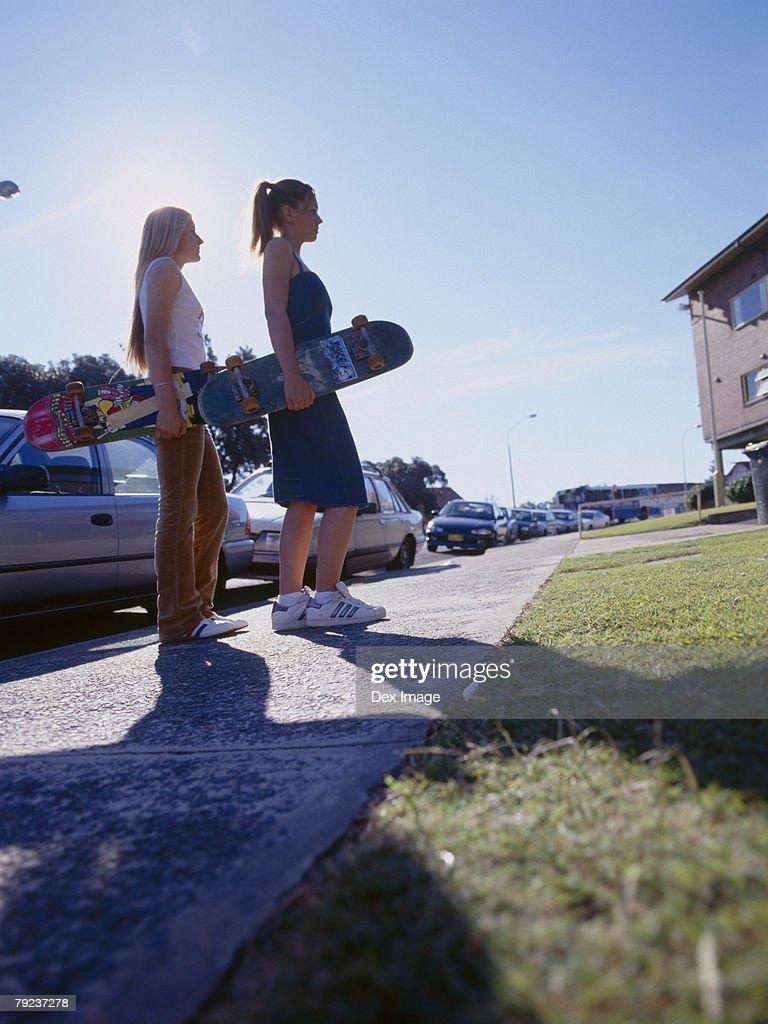 Two women walking on walkway holding skateboards, side view : Stock Photo