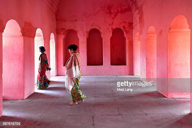 Two women walking through a colorful setting in the Buddhist pilgrimage complex of the Mahabodhi temple