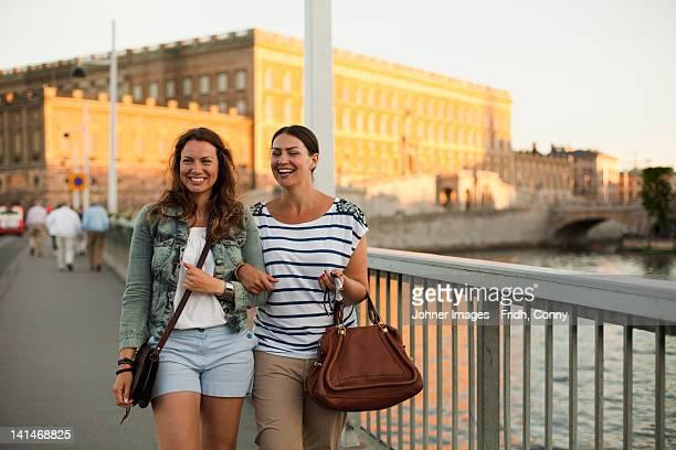 Two women walking through bridge, laughing