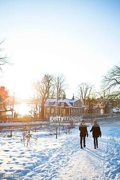 Two women walking through snow covered path