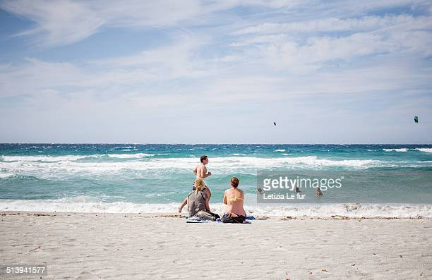 Two women watching a jogger on a beach in Corsica France