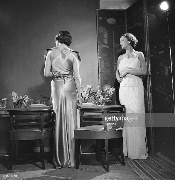 Two women wear evening gowns designed by French fashion designer Jeanne Lanvin October 1934