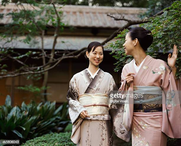 Two Women Wearing a Kimono Standing in a Garden, One Waving Goodbye