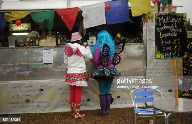 Two women wearing angel wings buy drinks during the second day of the Glastonbury 2013 Festival of Contemporary Performing Arts at Pilton Farm...