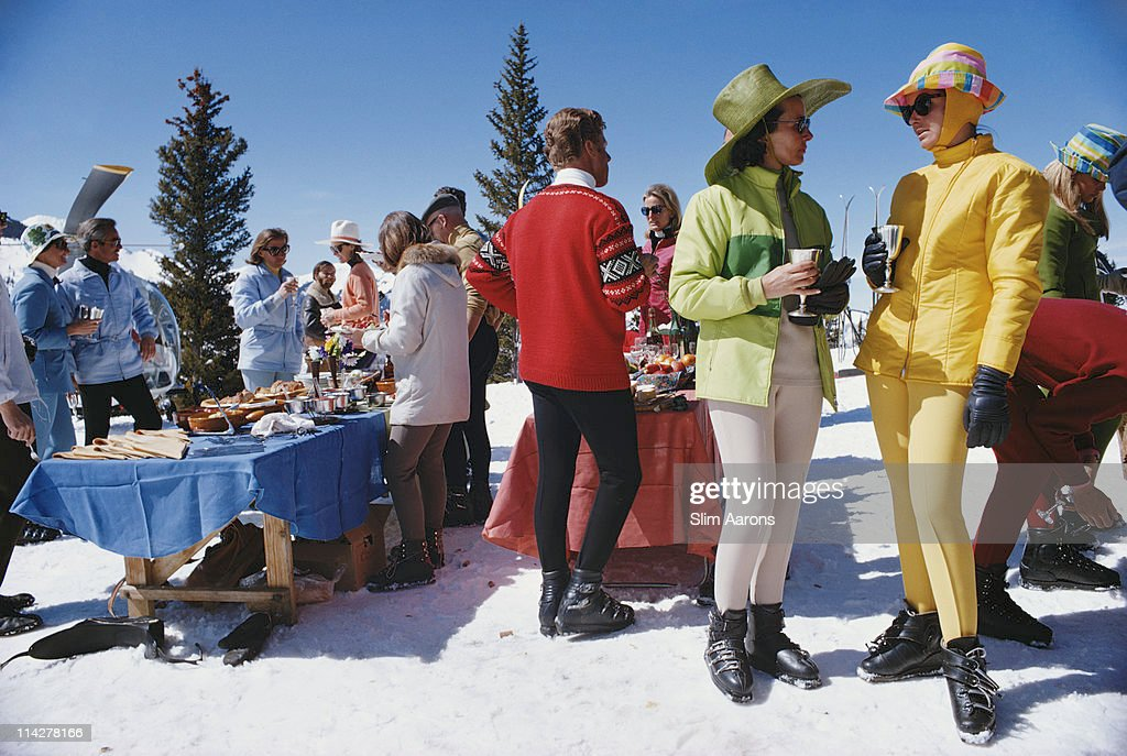 Two women wearing brightlycoloured skiwear stand in the foreground of a group of people attending a party in Snowmass Village in Pitkin County...