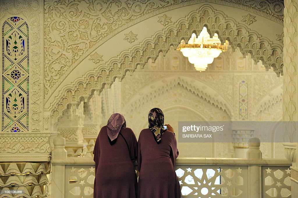Two women wearing headscarves look from a gallery during a service to inaugurate the new Omar Mosque in Berlin's Kreuzberg district during the inauguration of the Islamic Maschari Centre on May 21, 2010. The centre includes the mosque, a kindergarden, a school, a library, a travel agency and a shopping centre.