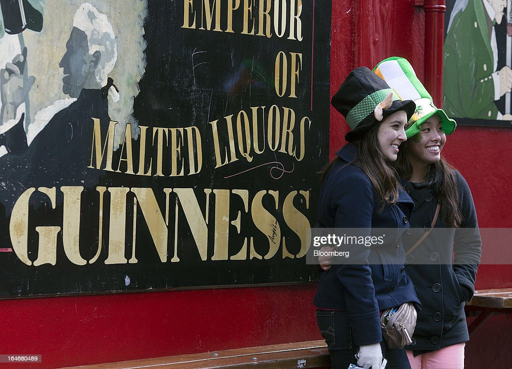 Two women wearing Irish-themed hats, a leprechaun, left, and a St. Patrick's day, stand and pose for a photograph outside a bar in the Temple Bar area of Dublin, Ireland, on Saturday, March 16, 2013. Ireland's renewed competiveness makes it a beacon for the U.S. companies such as EBay, Google Inc. and Facebook Inc., which have expanded their operations in the country over the past two years. Photographer: Simon Dawson/Bloomberg via Getty Images