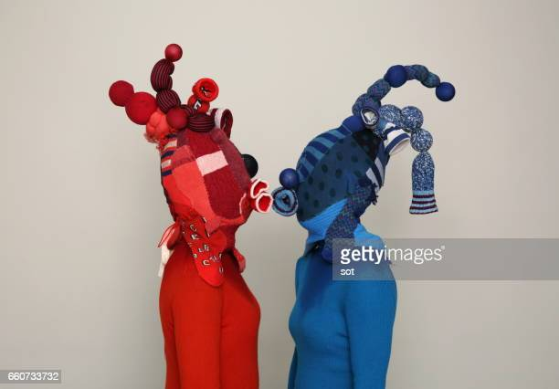 Two women wearing mask made of blue and red socks kissing,side view