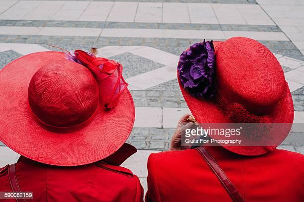 Two women wearing red hats
