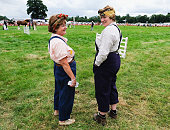 Two women wearing the period dress of the land army watch judging in the heavy horse category at the 150th Ryedale Agricultural Show on July 26 2016...