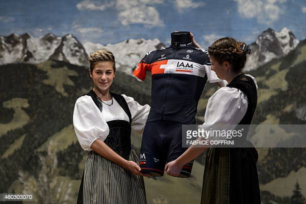Two women wearing traditionnal dress show the new outfit of IAM Cyling team during the presentation of the 2015 squad on December 11 2014 in Saanen...