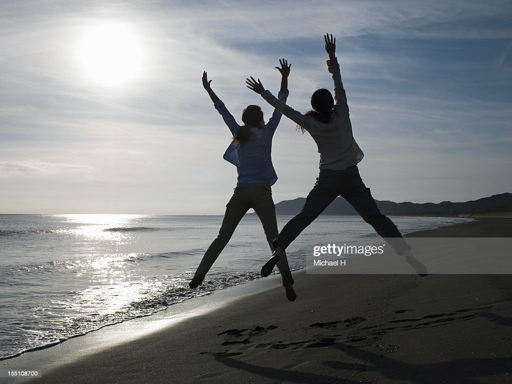 Two women who jump at the beach : Stock Photo