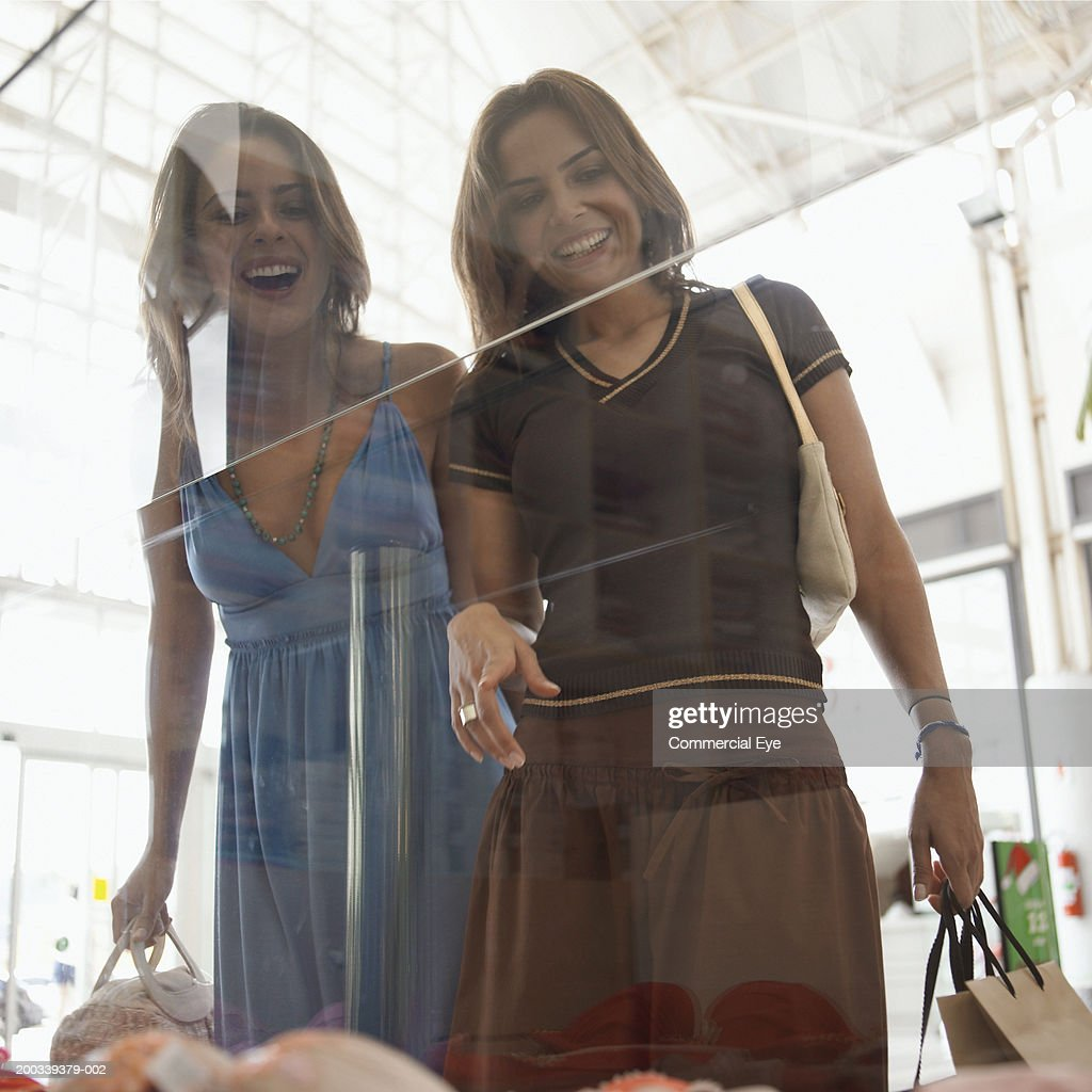 Two women window shopping, smiling, low angle view : Stock Photo