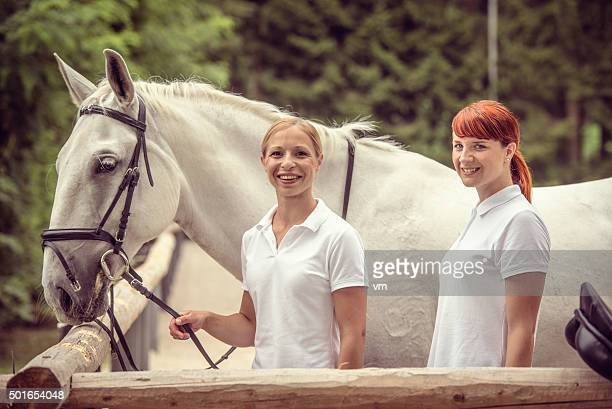 Two women with a white horse smiling
