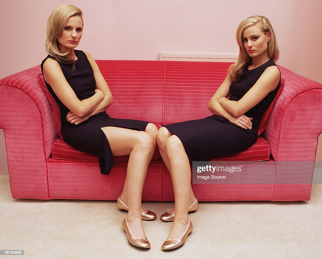 Two women with arms crossed on sofa : Stockfoto