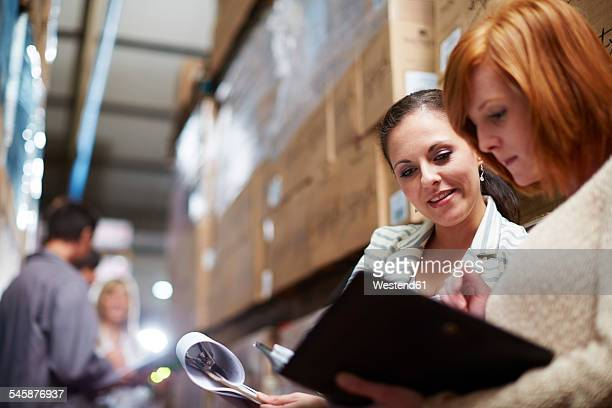 Two women with clipboard in warehouse