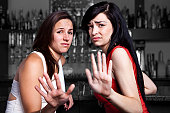 Two young women at a bar who don`t want to be harassed.