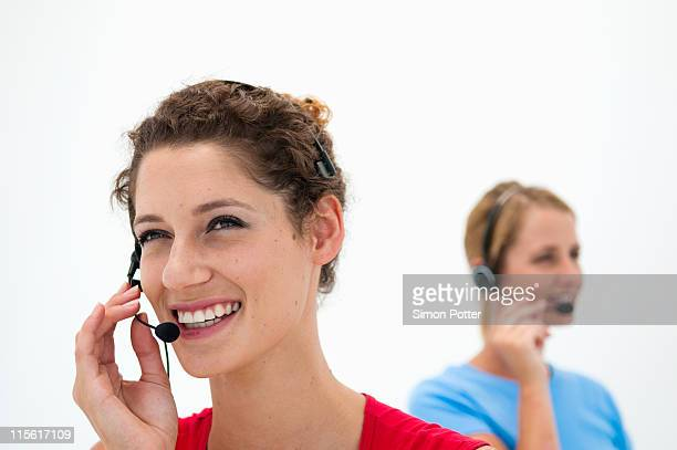 Two women with headsets in office