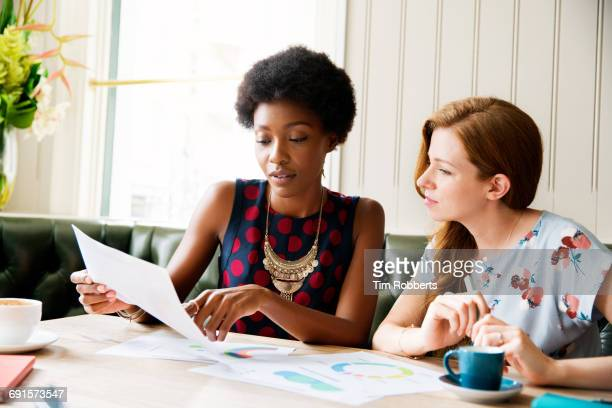 Two women with infographics at table.