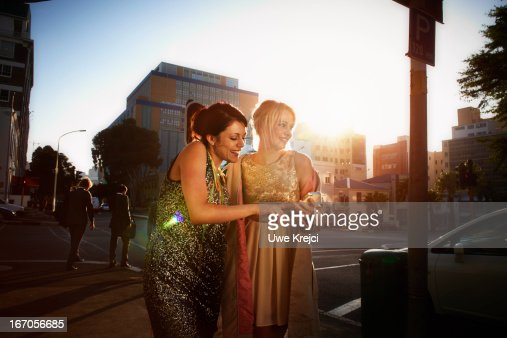 Two women with smart phone in hand outdoors : Stock Photo