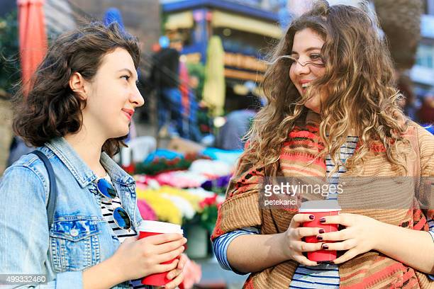 Two women with takeaway coffee cups in the city