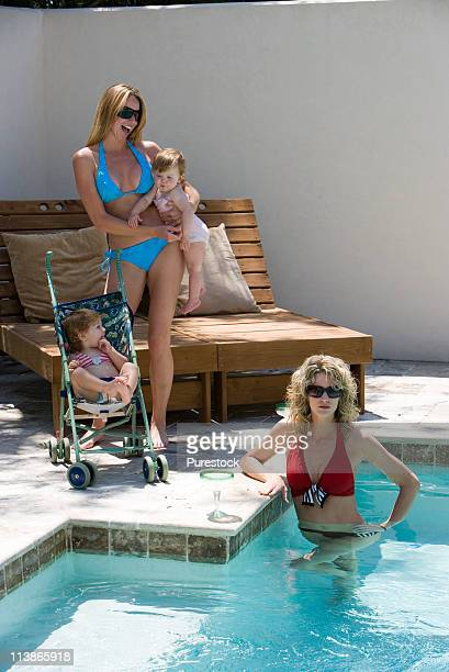 Two women with their babies poolside