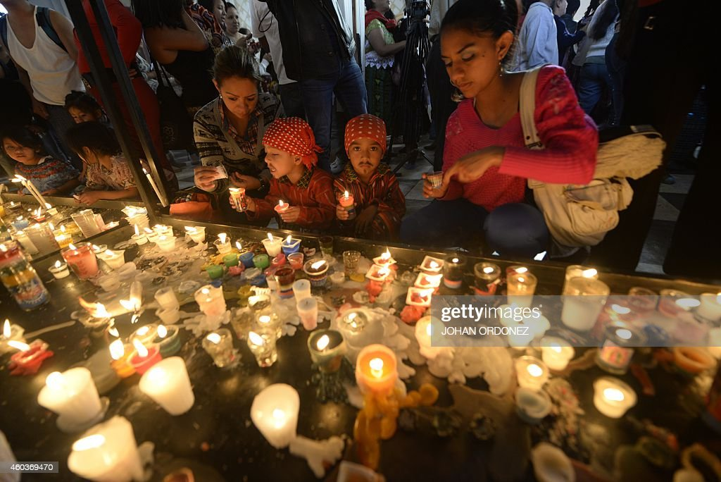 Two women with their children light candles on December 12 at the Basilica of the Virgin of Guadalupe in downtown Guatemala City during the...