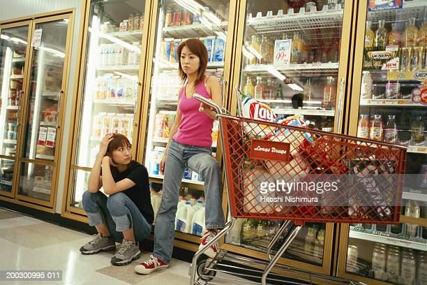 Two women with trolley in supermarket
