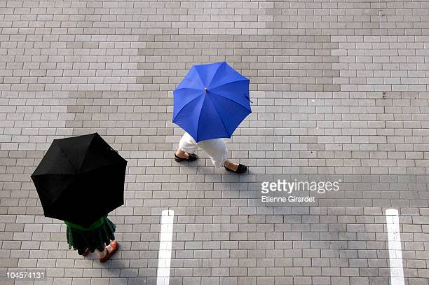 Two women with umbrellas walking through a parking lot