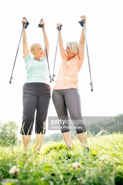 Two women with walking poles raised in air