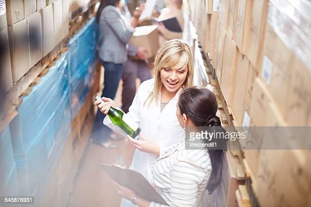 Two women with wine bottle in warehouse talking