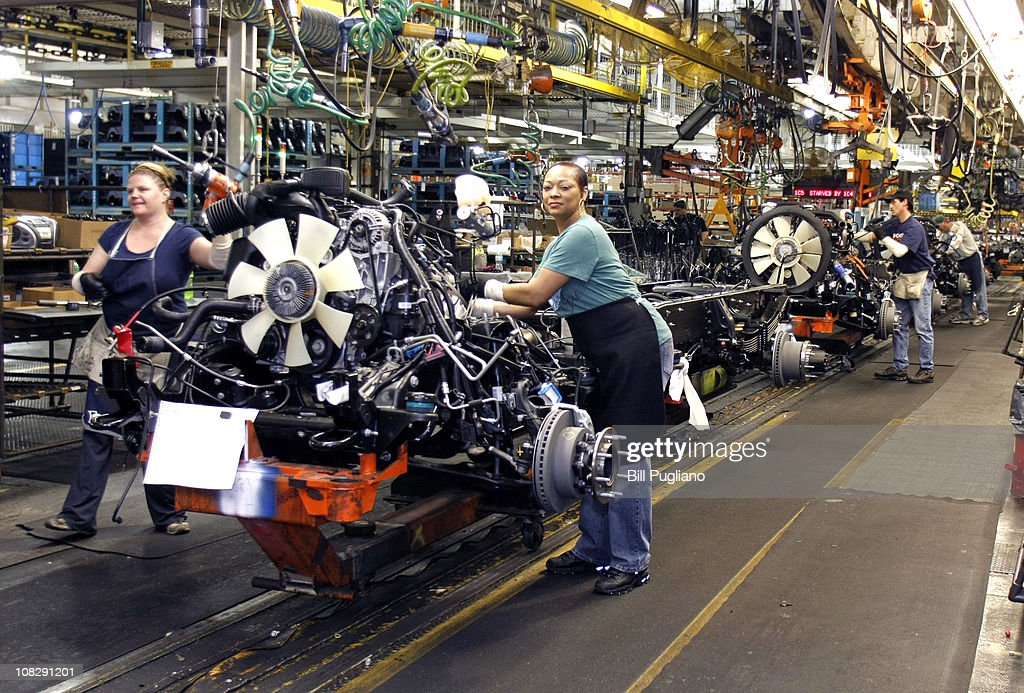 Two women work on the engine of a GM truck on the assembly line of the General Motors Flint Assembly Plant January 24 2011 in Flint Michigan In...