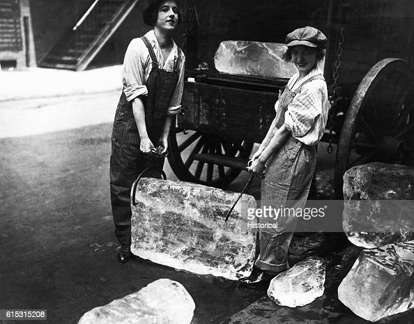 Two women working as ice deliverers carry a large block of ice from the back of a wagon using ice tongs Women had previously never worked in jobs...
