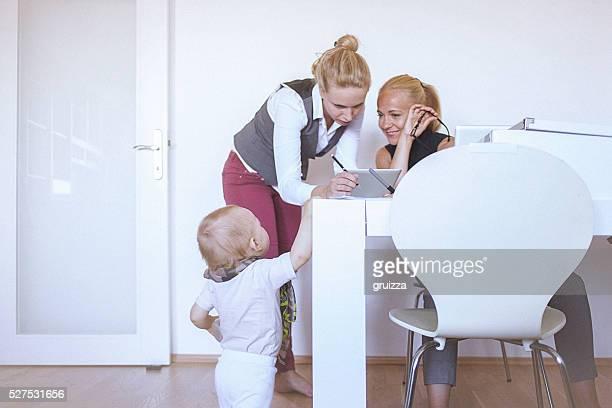 働く 2 人の女性が家庭では、赤ちゃん