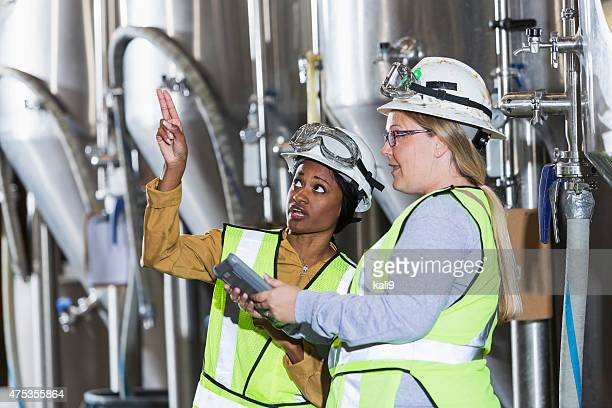 Two women working in a factory wearing hardhats