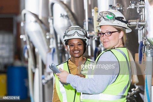 Two women working in a factory wearing hardhats