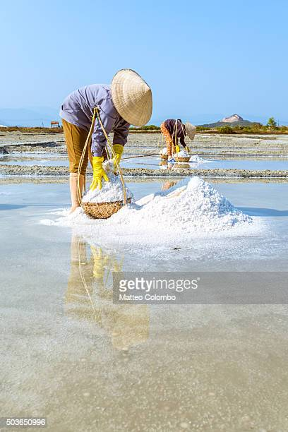 Two women working in a salt field, Vietnam