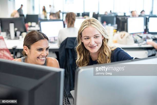 Two women working in office looking at computer, smiling