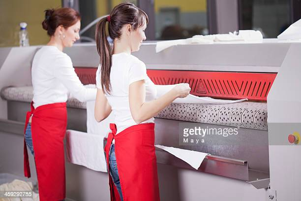 Two women working on an industrial ironing machine