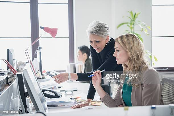 Two women working on computer in modern office