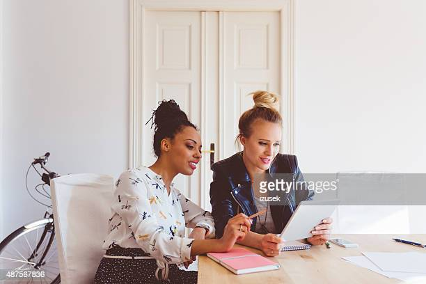 Two women working on digital tablet in an office