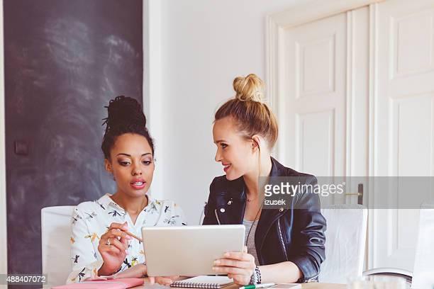 Duas mulheres a trabalhar em um tablet digital no escritório