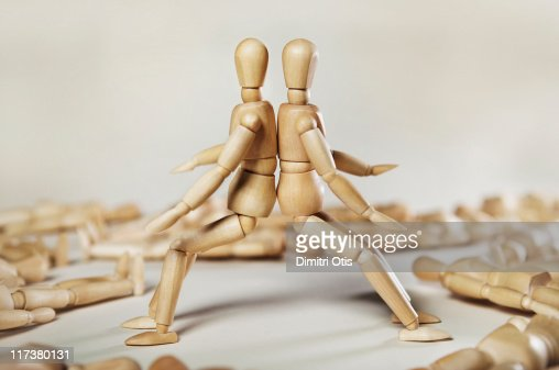 Two wood mannequins leaning against each other : Stock Photo