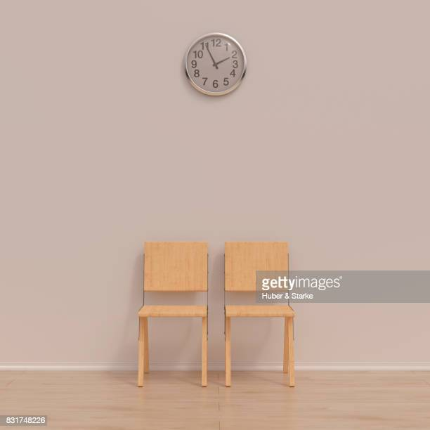 Two wooden chairs and a wall clock in a waiting room
